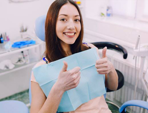 Woman smiling in dental chair giving thumbs up