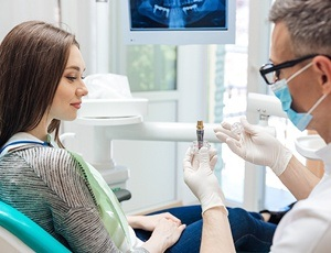 dentist demonstrating how dental implants work to a patient