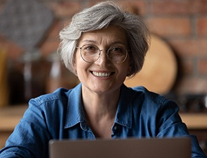 An older woman wearing glasses and showing off her new smile thanks to dental implants