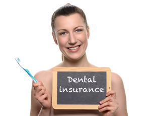 Smiling woman holding dental insurance sign