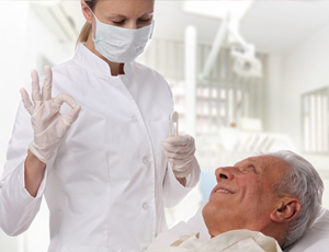 Dentist talking to senior man in dental chair