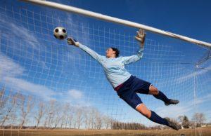 goalie blocking a soccer ball from entering net