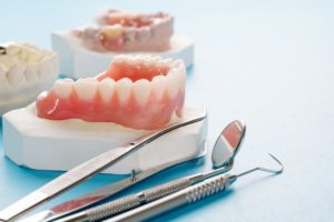 dentures sitting next to dental tools